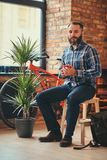 Handsome bearded hipster male in a blue fleece shirt and jeans holds a cup of morning coffee while sitting on a wooden stock photos