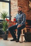 Handsome bearded hipster male in a blue fleece shirt and jeans holds a cup of morning coffee while sitting on a wooden stock image