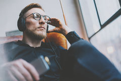 Portrait handsome bearded man glasses,headphones listening to music modern loft studio.Man sitting in vintage chair,holding smartp. Closeup photo handsome Stock Photography