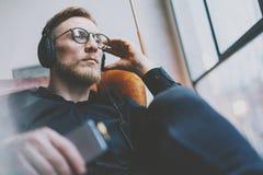 Portrait handsome bearded man glasses,headphones listening to music modern loft studio.Man sitting in vintage chair,holding smartp Stock Photography