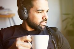 Portrait of handsome bearded man in headphones listening to music at home and drinking coffee. Relaxing and rest time