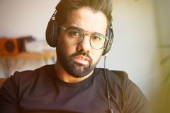 Portrait of handsome bearded man in headphones listening to music at home. Relaxing and rest time concept. Blurred royalty free stock photography