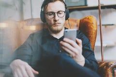 Portrait handsome bearded man headphones listening to music, watching video mobile phone modern loft studio.Man sitting in vintage Stock Photos