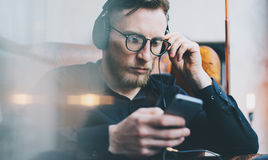 Portrait handsome bearded man headphones watching video mobile phone modern loft studio.Man sitting in vintage chair,holding smart Royalty Free Stock Photos