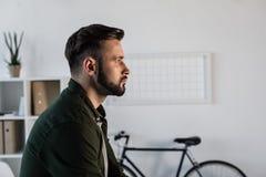 Portrait of handsome bearded man looking away in office. Profile portrait of handsome bearded man looking away in office Stock Photo