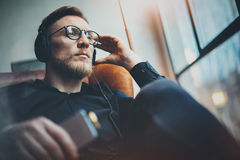 Portrait handsome bearded man wearing glasses,headphones listening to music at modern home.Guy sitting in vintage chair Royalty Free Stock Image