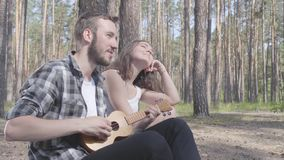 Portrait handsome bearded young man playing ukulele while pretty young happy woman sitting near. Loving couple having stock video footage