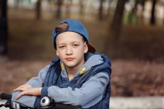 Portrait Handsome boy on a bicycle at asphalt road in the spring park. Royalty Free Stock Images