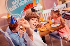 Portrait of handsome boy that demonstrating nameboard. Good for you. Cute kid expressing positivity while being on birthday party royalty free stock photo