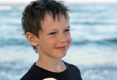 Portrait of a handsome boy with an Eupropean appearance. A sweet sunbathing baby boy smiles tenderly against the backdrop. Of the sea at sunset Stock Image
