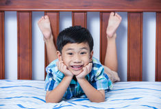 Portrait of handsome boy lying barefoot on bed in bedroom. Royalty Free Stock Photography