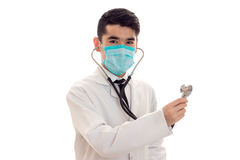 Portrait of handsome brunette male doctor in uniform and mask with stethoscope posing and looking at the camera isolated Royalty Free Stock Photography