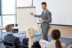 Business Coach Pointing at Graph. Portrait of handsome business coach giving presentation during training seminar in conference hall standing by whiteboard and Royalty Free Stock Images