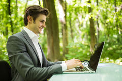 Portrait of young handsome business man in suit at laptop at office table in green forest park. Business concept. Portrait of handsome business man in suit at royalty free stock photos