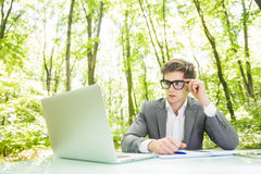 Portrait of young handsome business man in suit working at laptop at office table thinking in green forest park. Business concept. Portrait of handsome business royalty free stock images