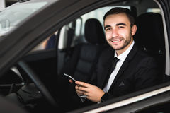 Portrait of handsome business man use phone in car Stock Photos