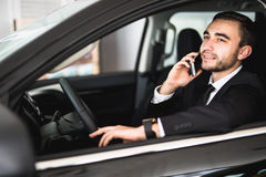 Portrait of handsome business man use phone in car Stock Image