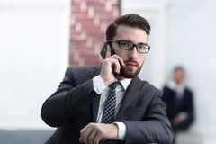 View of a Young attractive business man using smartphone. Portrait of handsome business man using cell phone Royalty Free Stock Image