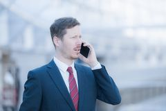 Business man is talking on the cellular phone. Portrait of a handsome business man wearing a suit a dark blue suit and a red neck tie, talking on the phone Royalty Free Stock Photos