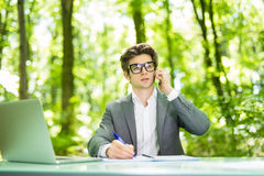 Portrait of young handsome business man working at laptop at office table and talk at phone with costumer and make notice in green. Portrait of handsome business royalty free stock photos