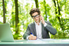 Portrait of young handsome business man working at laptop at office table and talk at phone with costumer and make notice in green. Portrait of handsome business royalty free stock photo