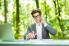 Portrait of young handsome business man working at laptop at office table and talk at phone with costumer and make notice in green. Portrait of handsome business stock images