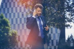 Portrait of handsome businessman communicating on mobile phone Stock Photos