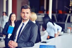 Portrait of an handsome businessman in front of his team stock photography