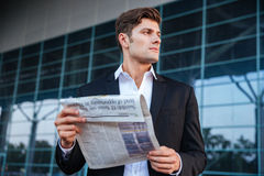 Portrait of a handsome businessman holding newspaper outdoors Royalty Free Stock Photos