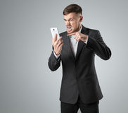 Portrait of a handsome businessman making  phone call against  grey background Stock Photos