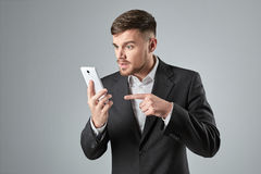 Portrait of a handsome businessman making  phone call against  grey background Royalty Free Stock Photos