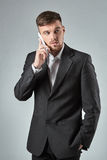 Portrait of a handsome businessman making  phone call against  grey background Royalty Free Stock Images