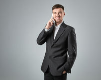 Portrait of a handsome businessman making  phone call against  grey background Stock Image