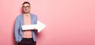 Handsome man in bright jacket with speech pointer. Portrait of handsome businessman in pink jumper, blue jacket and glasses holds blank paper speech arrow Stock Images
