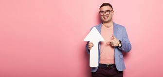 Handsome man in bright jacket with speech pointer. Portrait of handsome businessman in pink jumper, blue jacket and glasses holds blank paper speech arrow Royalty Free Stock Photography