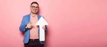 Handsome man in bright jacket with speech pointer. Portrait of handsome businessman in pink jumper, blue jacket and glasses holds blank paper speech arrow Stock Image