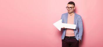 Handsome man in bright jacket with speech pointer. Portrait of handsome businessman in pink jumper, blue jacket and glasses holds blank paper speech arrow Stock Photo