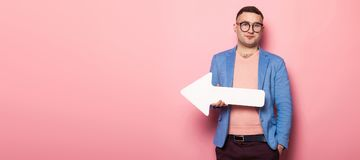 Handsome man in bright jacket with speech pointer. Portrait of handsome businessman in pink jumper, blue jacket and glasses holds blank paper speech arrow Royalty Free Stock Photos