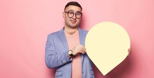 Handsome man in bright jacket with speech bubble. Portrait of handsome businessman in pink jumper, blue jacket and glasses holds blank paper thinking speech Stock Photo
