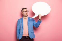 Handsome man in bright jacket with speech bubble. Portrait of handsome businessman in pink jumper, blue jacket and glasses holds blank paper thinking speech Royalty Free Stock Photo