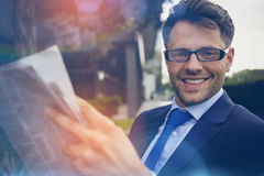 Portrait of handsome businessman reading newspaper Stock Photos
