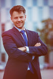 Portrait of handsome businessman standing with crossed arms. Portrait of handsome businessman standing with arms crossed outside office Stock Photo