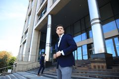 Portrait of a handsome businessman in a suit standing outside a city building. Royalty Free Stock Photo