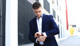 Portrait of a handsome businessman in a suit standing outside a city building. Stock Photography