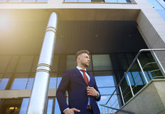 Portrait of a handsome businessman in a suit standing outside a city building. Royalty Free Stock Images
