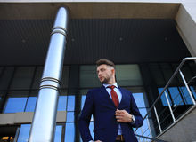 Portrait of a handsome businessman in a suit standing outside a city building. Stock Image