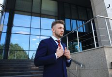 Portrait of a handsome businessman in a suit standing outside a city building. Royalty Free Stock Photography