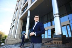 Portrait of a handsome businessman in a suit standing outside a city building. Royalty Free Stock Image