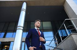 Portrait of a handsome businessman in a suit standing outside a city building. Stock Photo