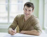 Portrait of handsome businessman writing on document at desk in office Royalty Free Stock Photo